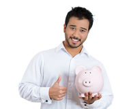 Young smiling student holding piggy bank showing thumbs up indicating a smart financial investment Stock Images