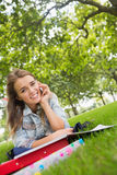 Young smiling student lying on the grass on the phone. On college campus Stock Photo
