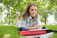 Young smiling student lying on the grass sending a text. On college campus Royalty Free Stock Image