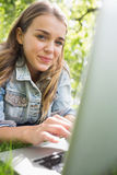 Young smiling student lying on the grass using her laptop. On college campus Royalty Free Stock Photo