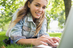 Young smiling student lying on the grass using laptop. On college campus Stock Images