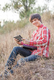 Young smiling student working in park Royalty Free Stock Photography