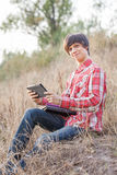 Young smiling student working in park Royalty Free Stock Photos