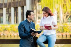 Young smiling students outdoors holding books. Smiling students learning for exam together in a city park. Students Brainstorming Meeting learning for exam. Fast stock photography