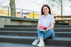 Young smiling students outdoors holding books. Smiling portrait of female university student sitting down on Campus stairs holding books looking to camera royalty free stock photography