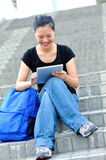 A young smiling students using a digital tablet. Portrait of a young smiling students using a digital tablet sitting on the steps on campus Royalty Free Stock Image