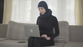 Young smiling successful confident girl in balck clothes and beautiful headdress working with her laptop sitting on the stock footage