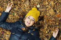 Young smiling teenage girl lying in the autumn leaves Royalty Free Stock Images