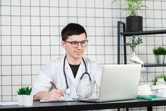 Young and smiling therapist in uniform filling up documents stock photo