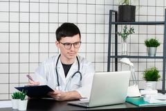 Young and smiling therapist in uniform filling up documents stock image