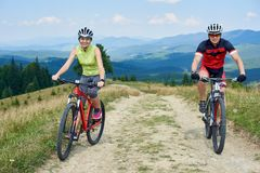 Young smiling tourists couple man and woman in professional sportswear cycling bikes down stock images