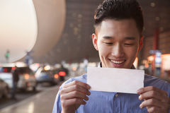 Young Smiling traveler looking at ticket at airport Stock Images