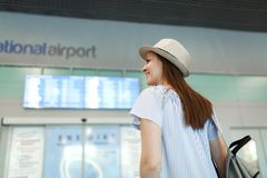 Young smiling traveler tourist woman in hat with backpack look on schedule, timetable, wait in lobby hall at stock photography