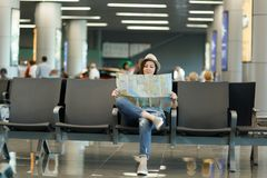 Young smiling traveler tourist woman holding paper map, search route waiting in lobby hall at international airport. Passenger traveling abroad on weekends royalty free stock image