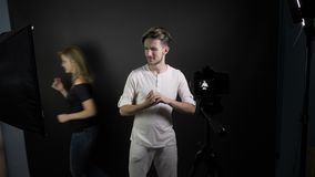 Young smiling vlogger man shooting for his vlog in a professional studio while girlfriend passes through the frame photobomb -. Young smiling vlogger man stock video