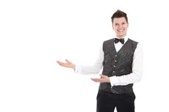 Young smiling waiter or butler gesturing welcome - isolated on w Stock Photo