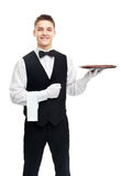 Young smiling waiter with empty tray Stock Photography