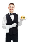 Young smiling waiter holding hamburger on plate Royalty Free Stock Photos