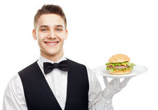Young smiling waiter holding hamburger on plate Royalty Free Stock Images