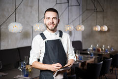 A young, smiling waiter in a restaurant, standing next to the tables with a glass of wine. Dressed in an apron, will Stock Photo