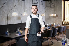 A young, smiling waiter in a restaurant, standing next to the tables with a glass of wine. Dressed in an apron, will Stock Photos