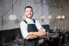 A young, smiling waiter in a restaurant, standing next to the tables with a glass of wine. He wears an apron, looks Stock Photos