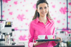 Young smiling waitress serving coffee at the bar Royalty Free Stock Images