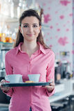 Young smiling waitress serving coffee at the bar Stock Photos