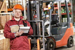 Warehouse worker in front of forklift Royalty Free Stock Photo