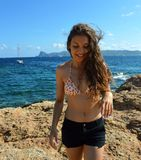 Young smiling wavy woman enjoying the wind in a sunny day in a rocky beach of Ibiza Island, Spain Royalty Free Stock Photos