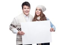 Young smiling winter couple holding big sign. Young casual caucasian brunette couple in winter clothing holding big sign and looking at camera with happy smile Stock Images