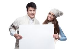 Young smiling winter couple holding big sign. Young casual caucasian brunette couple in winter clothing holding big sign and looking at camera with happy smile Stock Photo