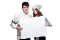 Young smiling winter couple holding big sign Stock Photo