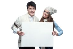 Young smiling winter couple holding big sign. Young casual caucasian brunette couple in winter clothing holding big sign and looking at camera with happy smile Stock Image