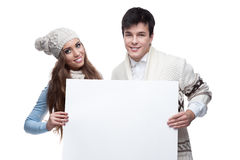 Young smiling winter couple holding big sign. Young casual caucasian brunette couple in winter clothing holding big sign and looking at camera with happy smile Royalty Free Stock Photography