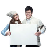 Young smiling winter couple holding big sign. Young casual caucasian brunette couple in winter clothing holding big sign and looking at camera with happy smile Royalty Free Stock Photos