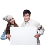 Young smiling winter couple holding big sign Stock Photography