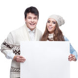 Young smiling winter couple holding big sign. Casual caucasian young couple in winter clothing holding big sign. isolated on white Royalty Free Stock Photos