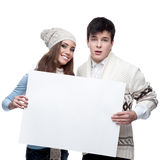 Young smiling winter couple holding big sign. Casual caucasian young couple in winter clothing holding big sign. isolated on white Royalty Free Stock Image