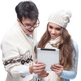Young smiling winter couple using tablet Royalty Free Stock Image