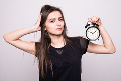 Young smiling woman with alarm clock  white grey wall background. Human face expression. Royalty Free Stock Photography