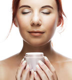 Young smiling woman applying cream on her face Stock Images