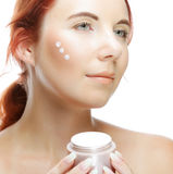 Young smiling woman applying cream on her face royalty free stock images