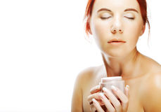 Young smiling woman applying cream on her face Stock Photography