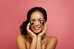 Young smiling woman applying face patch with hands Stock Photography