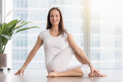 Young smiling woman in Ardha Matsyendrasana pose against floor w Royalty Free Stock Images