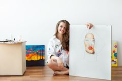 Young smiling woman artist sits on floor with unfinished masterpiece. Young smiling woman artist sits on floor and demonstrates unfinished masterpiece royalty free stock image
