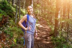 Young smiling woman with backpack hiking in forest royalty free stock images