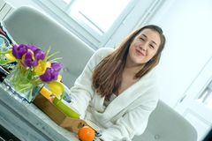 Young smiling woman in bathrobe sitting on the couch royalty free stock images
