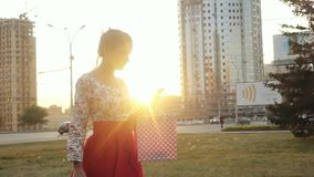 Young smiling woman in beautiful dress with shopping colorful bags using smartphone outdoors during sunset in slowmotion stock footage